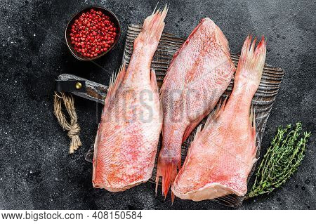 Raw Red Perch Or Seabass Fish On A Cutting Board. Black Background. Top View