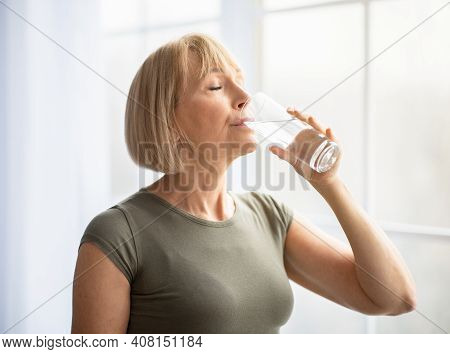 Fit Senior Woman Drinking Clear Water During Her Workout Break At Home. Mature Caucasian Lady Stayin