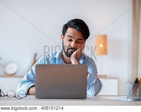 Boring Work. Young Arab Freelancer Guy Working On Laptop, Looking At Screen With Bored Face Expressi