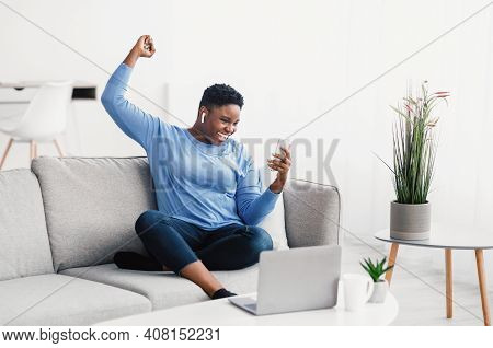 Yes. Excited Overjoyed African American Woman Using Smartphone Gadget, Shaking Clenched Fist, Scream