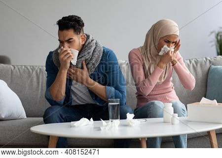 Sick Man And Woman In Hijab Got Coronavirus Or Cold, Sneezing Their Noses, Staying At Home During Il
