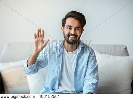 Greeting Concept. Portrait Of Friendly Eastern Man Waving Hello While Sitting On Couch At Home, Posi