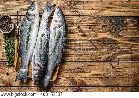 Raw Seabass Fish On A Tray. Wooden Background. Top View. Copy Space