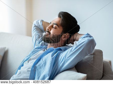 Relax Time. Portrait Of Handsome Arab Man Leaning Back On Couch With Closed Eyes, Keeping Hands Behi