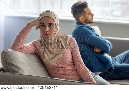 Upset Young Woman In Hijab Sitting By Her Sad Husband, Having Fight At Home. Muslim Couple Suffering