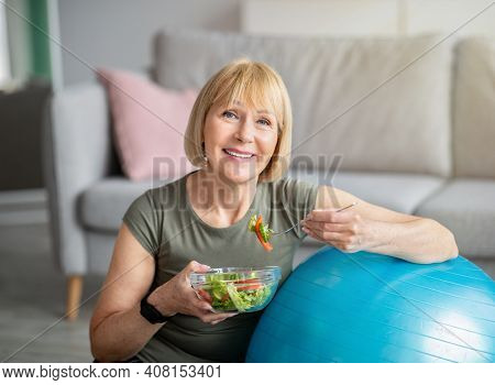 Exercise And Healthy Diet Concept. Senior Woman With Fitball Eating Fresh Vegetable Salad At Home. M