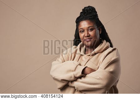 Minimal Waist Up Portrait Of Confident Curvy Woman Looking At Camera And Wearing Comfortable Hoodie