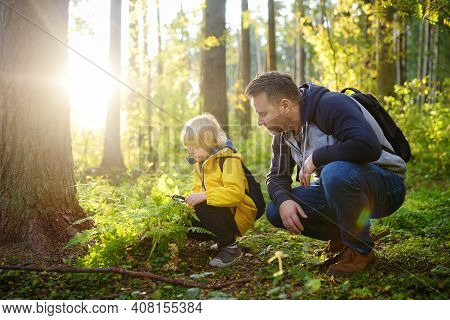 School Boy And His Father Hiking Together And Exploring Nature With Magnifying Glass. Child With His