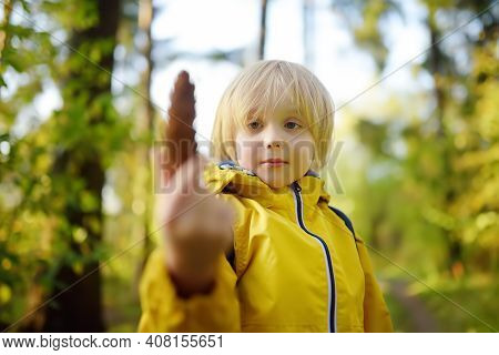 Schoolchild With Backpack Is Hiking And Exploring Nature In The Forest. Little Boy Travel In The Sun