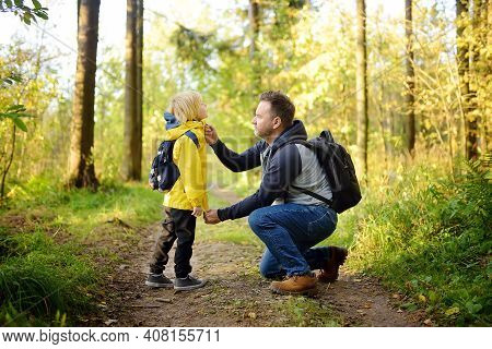 Cute Schoolchild And His Mature Father Hiking Together And Exploring Nature. Little Boy With His Dad