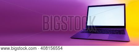 Slim Modern Laptop With White Screen On The Background Creative Light. Mockup In Colorful Bright Neo