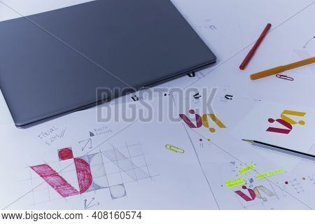 Creative Workplace Of A Graphic Designer With Laptop. Development Of A Logo For The Company. Drawing