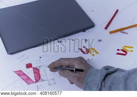Graphic Designer Designs A Logo Against A Background Of Sketches And Drawings On A Table. Printed Lo