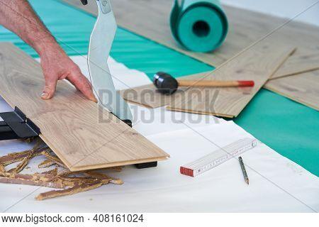 Man Is Cutting Laminate With Laminate Scissors. Preparing To Install Laminate.