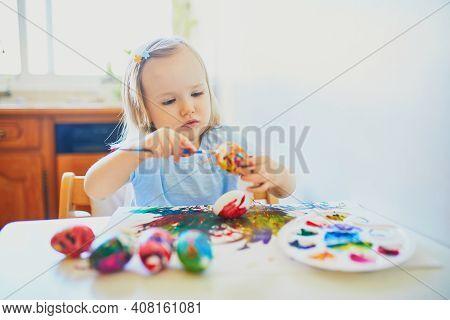 Adorable Little Girl Painting Eggs For Easter At Home, In Kindergaten Or Preschool. Celebrating Holi