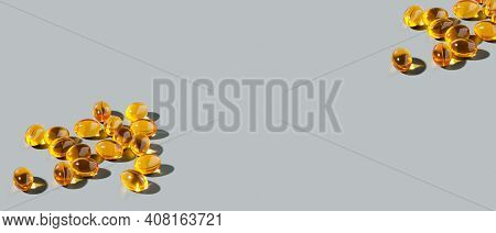 Yellow Gelatin Capsules On A Gray Background. Food Supplement, Vitamin D, Omega, Vitamin C, Multivit