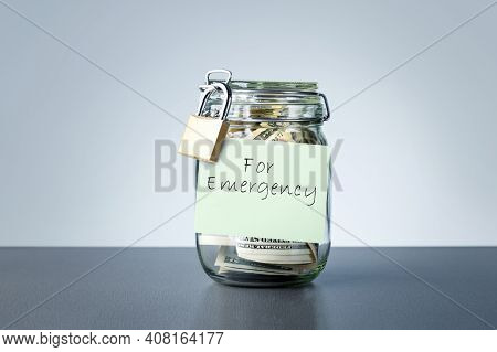 For Emergency Savings Written On The Jar With Dollars Banknotes Money. Concept Of Money Saving For R