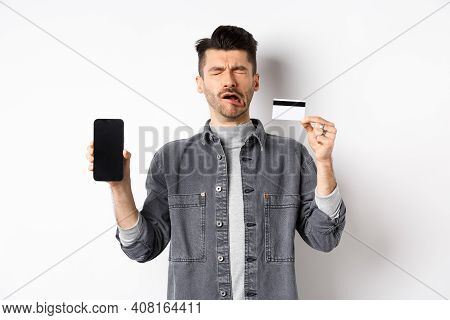 Sad Crying Man Show Empty Mobile Phone Screen And Plastic Credit Card, Standing Miserable On White B