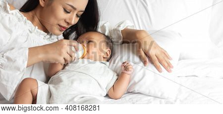 Portrait Of Enjoy Happy Love Family Asian Mother Playing With Adorable Little Asian Baby.mom Feeding