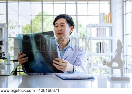 Asian Male Doctor Sitting In Hospital Cabin Reading And Analysing Issue In Lungs Of Patient With X-r