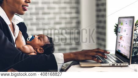 Portrait Of African American Black Mother Relaxing Using Technology Of Laptop Computer With Black Ba