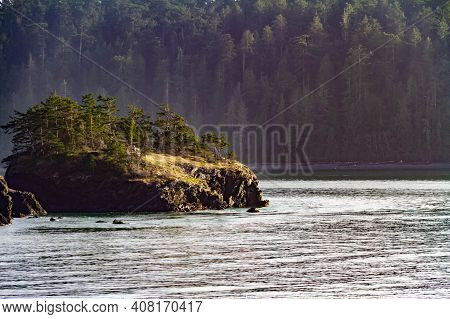 A Rock Outcropping Into The Ocean With Land Covered In Large Pine Trees In The Distance.