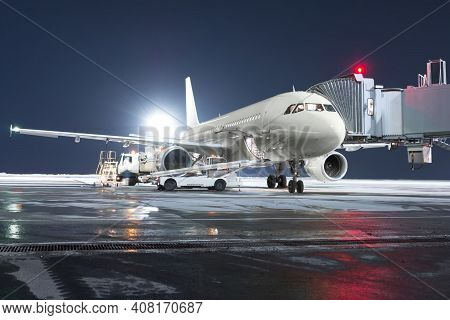 The Passenger Aircraft Stands At The Boarding Bridge On Night Airport Apron. The Baggage Compartment