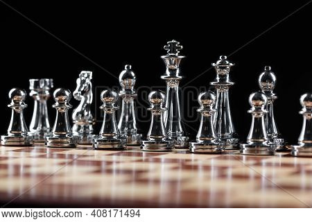 Silvery Chess Figures Standing On Wooden Chessboard. Intellectual And Tactical Game. Strategy Planni