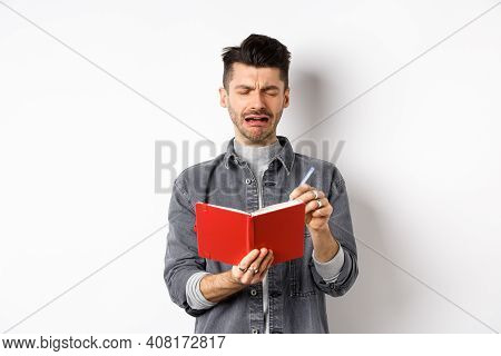 Sad Crying Guy Writing In His Diary With Miserable Face, Look Distressed While Making Notes In Journ