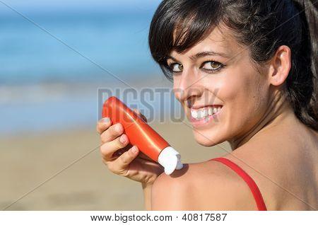Woman Protecting Skin With Suntan Lotion