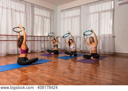 Group Of Young Womans With Magic Pilates Ring In Sportswear Leggings And Tops, Stretching In The Gym