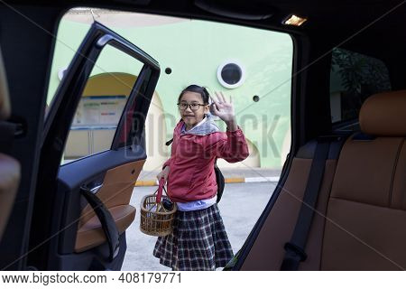 Portrait Of A Happy Child Withbackpack On His Back Move Her Hand After Get Off Car. Student Going To