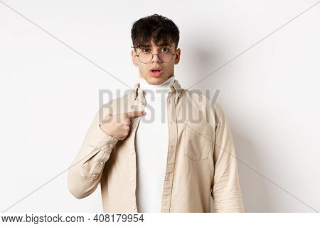 Confused And Surprised Young Man Pointing At Himself, Being Chosen Or Accused, Standing On White Bac