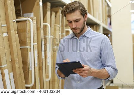Young Man Shopping Or Working In A Hardware Warehouse Standing Checking Supplies On His Tablet.
