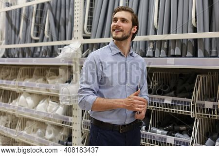 Portrait Of A Smiling Young Warehouse Worker Working In A Cash And Carry Wholesale Store.