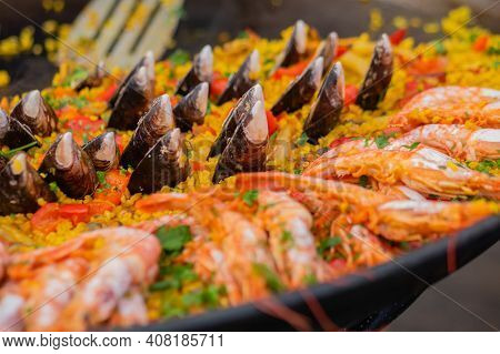 Cooked Yellow Paella With Shrimp, Mussel, Rice, Saffron In Huge Paella Pan At Summer Outdoor Food Ma