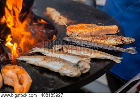 Process Of Grilling Salmon Steaks And Mackerel Fish On Black Brazier With Hot Flame At Summer Local