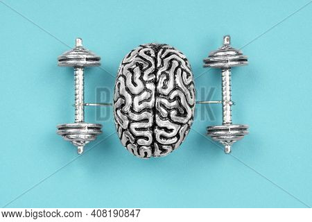 Creative Composition Made Of A Steel Copy Of A Human Brain Lifting Dumbbells. The Concept Of Brain E