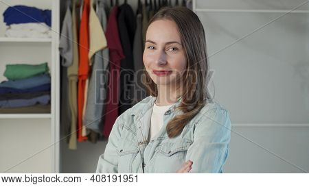 Portrait Of A Woman Who Stands Against The Background Of A Large Wardrobe A Wardrobe With Stylish Cl