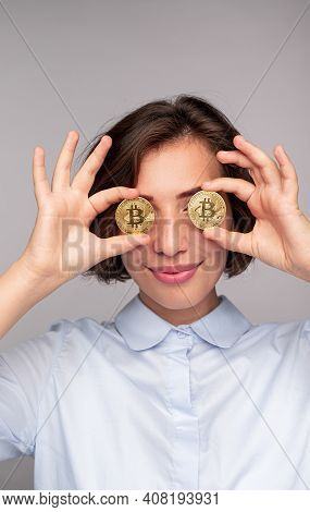 Playful Young Female In Shirt Smiling And Holding Bitcoins Near Eyes Against Gray Background