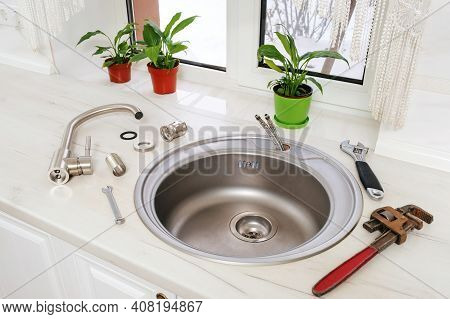 New Faucet And Tools For Installing Into The Kitchen Sink, Plumbing Work Or Renovation Concept.