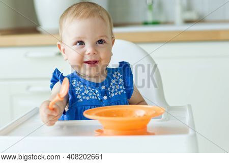 A Small Child In A High Chair Feeds Himself. High Quality Photo.