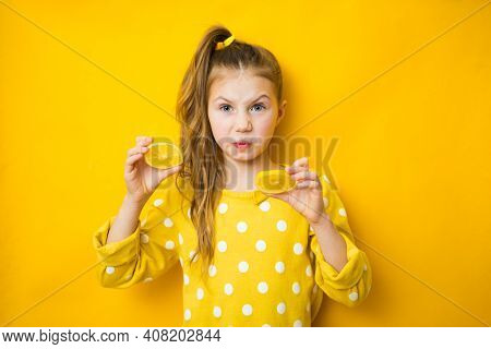 Emotional Young Girl With Cut Lemon On Yellow Background, Space For Text. Vitamin Rich Food