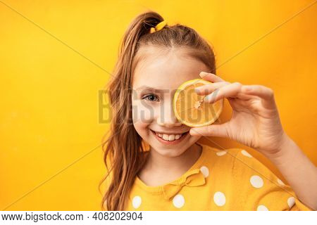 Happy Cute Girl With Clean Perfect Skin Hiding Eye Behind Lemon Slice On Yellow Background
