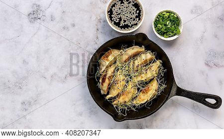 Asian Vegetarian Dumplings Gyozas Potstickers Fried On Cast-iron Pan, Served With Bowls Of Soy Sesam