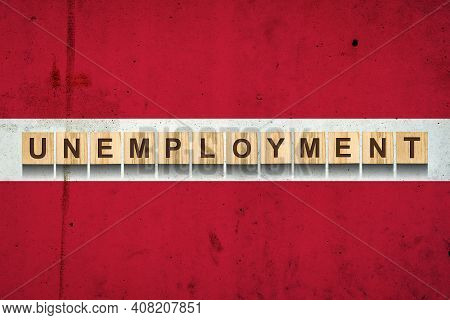 Unemployment. The Inscription On Wooden Blocks On The Background Of The Latvia Flag. Unemployment Gr