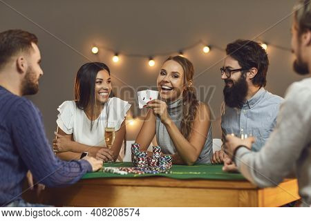 Happy Young Woman Showing Two Aces While Playing Poker With Her Friends.