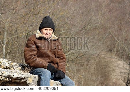 Portrait Of Elderly Man In Knitted Hat Sitting On The Rock In A Mountain Forest. Concept Of Harsh Hi