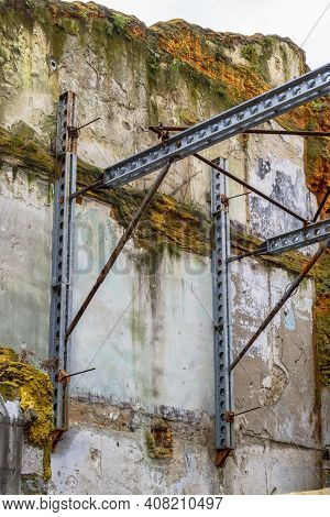 Steel Beams Supporting An Old Mossy Wall Of A Destroyed Building