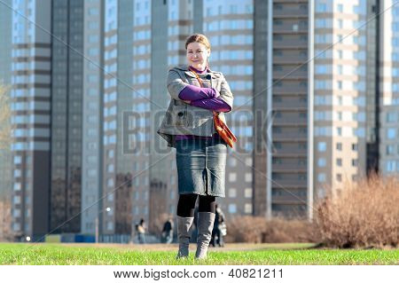 Yuong Woman Full-length Standing On Field Against Building Facade
